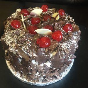 Pão-de-ló chocolate, recheado com chantilly e calda de ginja, coberto a chantilly , raspas de chocolate e cerejas